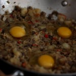 Make three (or four) dents in the hash and crack eggs into them.  Cover pan and let the steam cook the eggs.