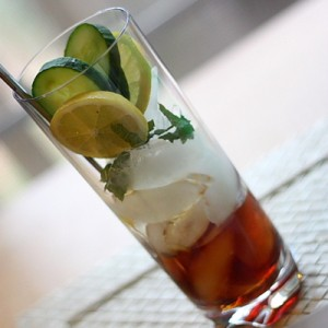 Fill a glass with ice.  Place two lemon slices, three cucumber slices and 3 chiffonaded mint leaves.  Fill glass 1/3 full with Pimm's.