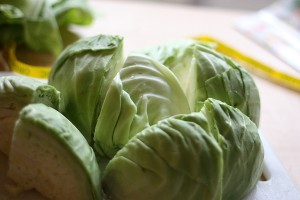 Peel the outer leaves off a head of green cabbage and cut into 8 pieces, removing the core in the process.