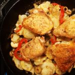 braised chicken in a cast iron pan with garlic, potatoes, olives
